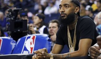 FILE - In this March 29, 2018, file photo, rapper Nipsey Hussle watches an NBA basketball game between the Golden State Warriors and the Milwaukee Bucks in Oakland, Calif. Hussle, 33, was shot and killed outside his Los Angeles clothing store on March 31, 2019. A year after Hussle's death, his popularity and influence are as strong as ever. He won two posthumous Grammys in January, he remains a favorite of his hip-hop peers and his death has reshaped his hometown of Los Angeles in some unexpected ways. (AP Photo/Marcio Jose Sanchez, File)