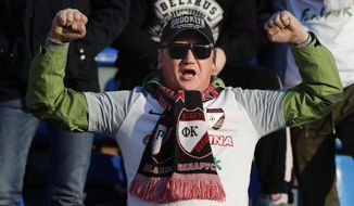 In this photo taken on Friday, March 27, 2020, a fan of Belshina Bobruisk team cheers during the Belarus Championship soccer match between Torpedo-BelAZ Zhodino and Belshina Bobruisk in the town of Zhodino, Belarus. Longtime Belarus President Alexander Lukashenko is proudly keeping soccer and hockey arenas open even though most sports around the world have shut down because of the coronavirus pandemic. The new coronavirus causes mild or moderate symptoms for most people, but for some, especially older adults and people with existing health problems, it can cause more severe illness or death. (AP Photo/Sergei Grits)