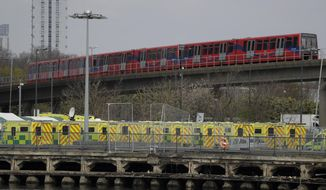 A line of London ambulances outside the ExCel center, which is being turned into a 4000 bed temporary hospital called NHS Nightingale to deal with coronavirus patients, as a train passes by in London, Monday, March 30, 2020. The new coronavirus causes mild or moderate symptoms for most people, but for some, especially older adults and people with existing health problems, it can cause more severe illness or death.(AP Photo/Matt Dunham)