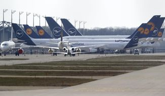 German Lufthansa planes sit parked in a line at the airport in Munich, Germany, Thursday, March 26, 2020. The planes are not in use because of the novel coronavirus outbreak. The new coronavirus causes mild or moderate symptoms for most people, but for some, especially older adults and people with existing health problems, it can cause more severe illness or death. (AP Photo/Matthias Schrader)