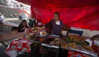 A woman serves tacos at a street restaurant at San Andres Mixquic, just outside Mexico City, Monday, March 30, 2020, amid the worldwide spread of the new coronavirus. (AP Photo/Fernando Llano)