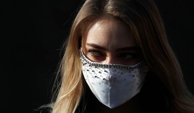 A woman wearing a homemade face mask poses for a photo downtown Prague, Czech Republic, Friday, March 27, 2020. In Czech Republic it is mandatory that all people must cover their mouths and noses in public to stem the spread of the novel coronavirus called COVID-19. (AP Photo/Petr David Josek)