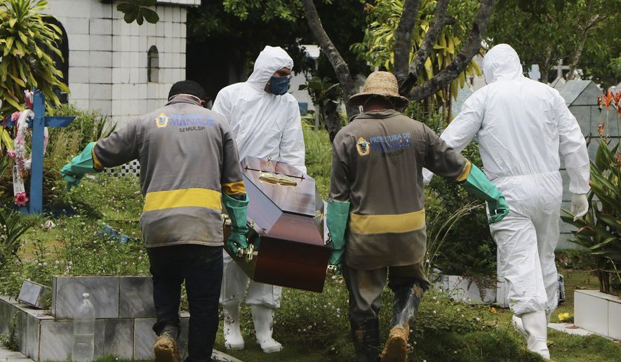 Funeral workers in protective clothes, and cemetery workers, carry the coffin of Robson de Souza Lopes at the Parque Taruma cemetery in Manaos, Brazil, Tuesday, March 31, 2020. According to authorities at the Amazonas Health Secretary, the 43-year-old musician died Monday after being diagnosed with COVID-19. (AP Photo/Edmar Barros)