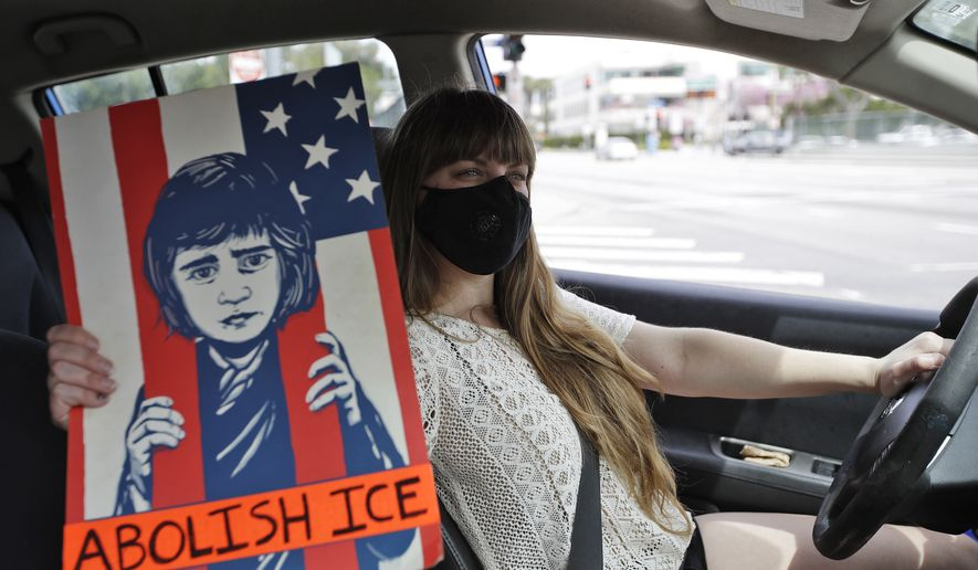 A protester holds a sign inside her car during a car-based protest outside of the Edward R. Roybal Federal Building Tuesday, March 31, 2020, in Los Angeles. Demonstrators across California coordinated efforts in a car-based protest to demand the release of immigrants in California detention centers over concerns over the COVID-19 pandemic. (AP Photo/Marcio Jose Sanchez)