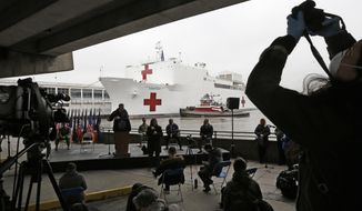 A journalist records speakers at a press briefing following the arrival of the USNS Comfort, a naval hospital ship with a 1,000 bed-capacity, Monday, March 30, 2020, at Pier 90 in New York. The ship will be used to treat patients who do not have the new coronavirus as land-based hospitals fill up to capacity with those that do. (AP Photo/Kathy Willens)