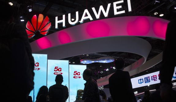 In this Oct. 31, 2019, file photo, attendees walk past a display for 5G services from Chinese technology firm Huawei at the PT Expo in Beijing. (AP Photo/Mark Schiefelbein, File)