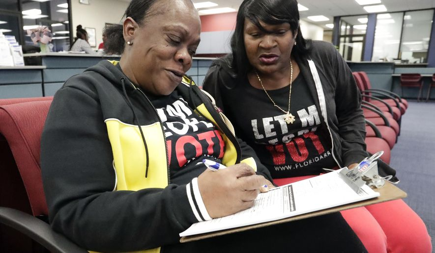 In this Jan. 8, 2019, photo, former felon Yolanda Wilcox, left, fills out a voter registration form as her best friend Gale Buswell looks on at the Supervisor of Elections office in Orlando, Fla. In a ruling Thursday, Tuesday, March 31, 2020, the 11th U.S. Circuit Court of Appeals declined to hear an appeal from Florida Gov. Ron DeSantis to limit the reach on Amendment 4, the ballot measure approved overwhelmingly by voters in 2018 that allowed felons to regain the right to vote. (AP Photo/John Raoux) **FILE**