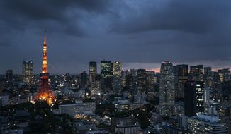 FILE-In this May 29, 2019 file photo the Tokyo Tower is lit up at dusk as rain clouds hover over Tokyo's skyline. Patricia Espinosa, Executive Secretary of the United Nations Framework Convention on Climate Change, on Tuesday chided Japan over its new plan to reduce greenhouse gas emission. Environmental campaigners say Tokyo's new proposal shows no real ambition to increase existing efforts. (AP Photo/Jae C. Hong)