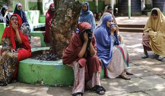"""Relatives and friends wait outside as the body of 13-year-old Yasin Hussein Moyo is washed prior to burial, at the Kariakor cemetery in Nairobi, Kenya Tuesday, March 31, 2020. The family of a 13-year-old boy is in mourning after police in Kenya's capital are accused of shooting him dead while enforcing a coronavirus curfew. Kenya's police inspector general has ordered an investigation into the boy's death by """"stray bullet,"""" including a forensic analysis of all firearms held by officers at the scene.  (AP Photo/Brian Inganga)"""