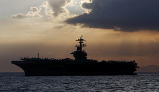 In this April 13, 2018, photo the USS Theodore Roosevelt aircraft carrier is anchored off Manila Bay west of Manila, Philippines. The captain of the U.S. Navy aircraft carrier facing a growing outbreak of the coronavirus is asking for permission to isolate the bulk of his roughly 5,000 crew members on shore, which would take the warship out of duty in an effort to save lives. The ship is docked in Guam (AP Photo/Bullit Marquez) **FILE**
