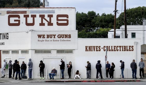 In this March 15, 2020, file photo, people wait in line to enter a gun store in Culver City, Calif. (AP Photo/Ringo H.W. Chiu, File)