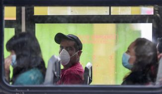 "Commuters wear masks as they ride a bus, to prevent the spread of the new coronavirus in Mexico City, Tuesday, March 31, 2020. Mexico's government has broadened its shutdown of ""non essential activities,"" and prohibited gatherings of more than 50 people as a way to help slow down the spread of COVID-19. The one-month emergency measures will be in effect from March 30 to April 30. (AP Photo / Eduardo Verdugo)"