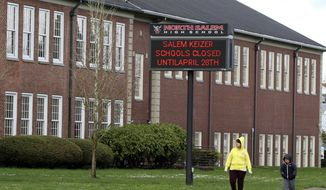 A woman and child walk past North Salem High School on Tuesday, March 31, 2020, which like all schools in Oregon, is closed until April 28, 2020, because of the coronavirus. Facing an expected closure through the end of the academic year, schools across Oregon have been told to begin distance learning on April 13, 2020. (AP Photo/Andrew Selsky)  **FILE**