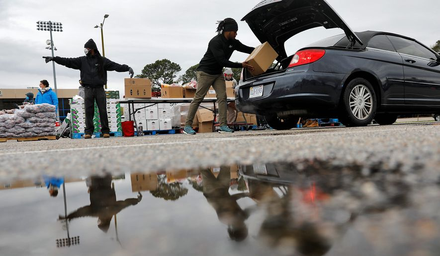 Volunteers with the Virginia Peninsula Foodbank distribute boxes of goods to people waiting in their vehicles in Newport News, Virginia, on Wednesday. Virginia, whose population tops 8.5 million, reported 1,484 COVID-19 cases and 34 deaths. (Associated Press)