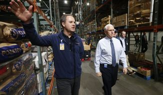 Vice President Mike Pence, right, walks with Walmart president and CEO Doug McMillon, as they tour a Walmart Distribution Center Wednesday March 1, 2020, in Gordonsville, Va. (AP Photo/Steve Helber)