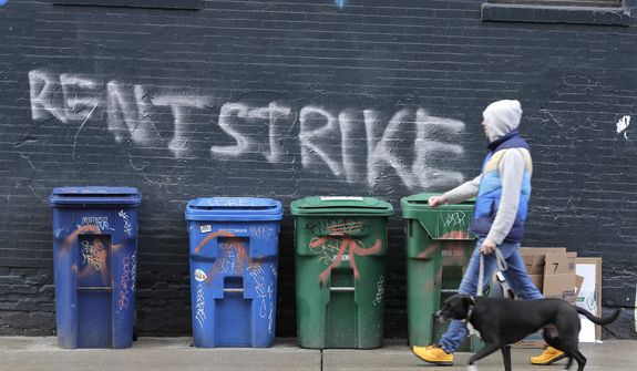 """A pedestrian walks past graffiti that reads """"Rent Strike"""" Wednesday, April 1, 2020, in Seattle's Capitol Hill neighborhood. With millions of people suddenly out of work and rent due at the first of the month, some tenants in the U.S. are vowing to go on a rent strike until the new coronavirus pandemic subsides. Some cities have temporarily banned evictions, but advocates for the strike are demanding that rent payments be waived, not delayed, for those in need during the crisis. (AP Photo/Ted S. Warren)"""