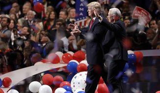 In this July 21, 2016, file photo, Republican presidential candidate Donald Trump, center left, walks with vice presidential candidate Gov. Mike Pence of Indiana as confetti and balloons fall during celebrations after Trump's acceptance speech on the final day of the Republican National Convention in Cleveland. The coronavirus pandemic is forcing Democrats and Republicans to take a close look at whether they'll be able to move forward as planned this summer with conventions that typically kick off the general election season. (AP Photo/Matt Rourke, File)