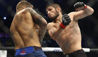 """FILE - In this Sept. 7 2019, file photo, Russian UFC fighter Khabib Nurmagomedov, right, fights with UFC fighter Dustin Poirier, of Lafayette, La., during lightweight title mixed martial arts bout at UFC 242 in Yas Mall in Abu Dhabi, United Arab Emirates. Nurmagomedov says he won't leave quarantine in Russia to fight, dealing another blow to UFC President Dana White's determination to hold UFC 249 in two weeks amid the coronavirus pandemic. Nurmagomedov made his announcement Wednesday, April 1, 2020, on Instagram, telling the mixed martial arts world to """"take care of yourself and put yourself in my shoes."""" (AP Photo/Mahmoud Khaled, File)"""