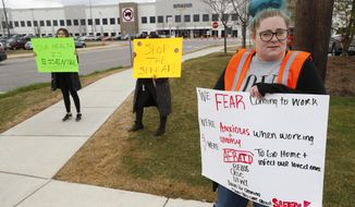 Employee Tonya Ramsay, right, holds a sign outside the Amazon DTW1 fulfillment center in Romulus, Mich., Wednesday, April 1, 2020. Employees and family members are protesting in response to what they say is the company's failure to protect the health of its employees amid the new coronavirus COVID-19 outbreak. (AP Photo/Paul Sancya)