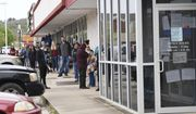 In this Monday, March 30, 2020, photo, a line of around 50 people extends from the door of Arkansas Workforce Center in Fayetteville, Ark. For information about small business loans and applying for Arkansas unemployment benefits, go to www.arkansasedc.com/covid19. (JT Wampler/The Northwest Arkansas Democrat-Gazette via AP)
