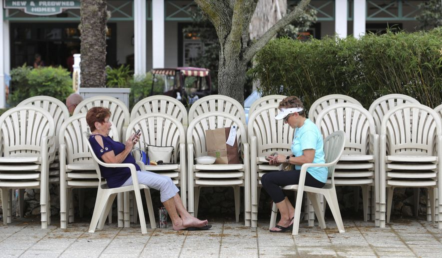 Residents of The Villages, Fla., keep social-distancing in a deserted town square at Lake Sumter Landing, Monday, March 23, 2020. Many of the businesses in the market square are closed in response to the coronavirus crisis. (Joe Burbank/Orlando Sentinel via AP)
