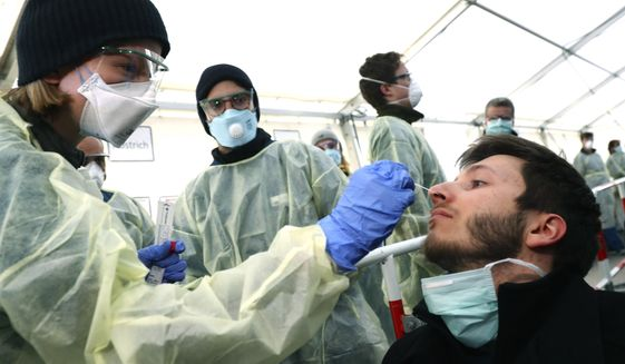 In this March 23, 2020, file photo, medical employees demonstrate testing, at a coronavirus test center for public service employees, during a media presentation in Munich, Germany. Labs were quick to ramp up their testing capacity and now experts say up to 500,000 tests can be conducted in Germany per week. That quick work, coupled with the country's large number of intensive care unit beds and its early implementation of social distancing measures, could be behind Germany's relatively low death toll. (AP Photo/Matthias Schrader, File)
