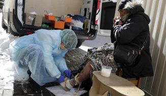 A member of a group of volunteer doctors of the Dom Druzei (Home of Friends) NGO gives a homeless person basic medical help in Moscow, Russia, Wednesday, April 1, 2020. As Moscow goes into lockdown amid the coronavirus pandemic, thousands of homeless people have trouble receiving food, water and shelter as Russia's capital closes nonessential businesses, cafes and parks. The new coronavirus causes mild or moderate symptoms for most people, but for some, especially older adults and people with existing health problems, it can cause more severe illness or death. (AP Photo/Pavel Golovkin)