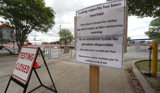 Signs placed outside a barricaded entrance to a coronavirus testing location state the location is closed for the day in Dallas, Tuesday, March 31, 2020. (AP Photo/Tony Gutierrez)