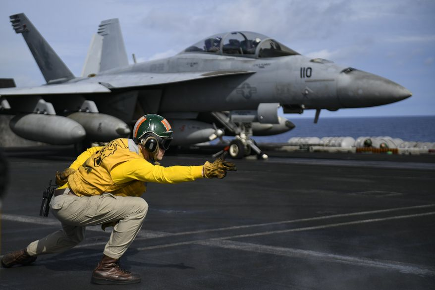 PACIFIC OCEAN (May 2, 2018) Lt. Adam Hall signals for an F/A-18F Super Hornet assigned to the Fighting Redcocks of Strike Fighter Attack Squadron (VFA) 22 to launch on the flight deck of the aircraft carrier USS Theodore Roosevelt (CVN 71). (U.S. Navy photo)