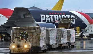 Palettes of N95 respirator masks are off-loaded from the New England Patriots football team's customized Boeing 767 jet on the tarmac, Thursday, April 2, 2020, at Logan Airport in Boston, after returning from China. The Kraft family deployed the Patriots team plane to China to fetch more than one million masks for use by front-line health care workers to prevent the spread of the coronavirus. (Jim Davis/The Boston Globe via AP, Pool)