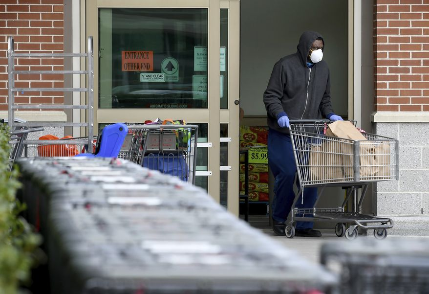 A customer leaves the Market Basket supermarket in South Attleboro, Mass. Thursday, April 2, 2020. Market Basket has instituted new protocols in their stores to allow more distancing between customers amid the growing coronavirus pandemic. The stores are limiting the number of customers shopping at one time depending on the size of the store with only one designated entrance and exit monitored by store associates. (Mark Stockwell/The Sun Chronicle via AP)