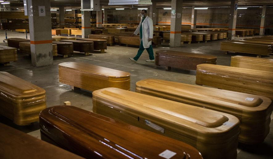 In this file photo, coffins with the bodies of victims of coronavirus are stored waiting for burial or cremation at the Collserola morgue in Barcelona, Spain, Thursday, April 2, 2020. (AP Photo/Emilio Morenatti) **FILE**