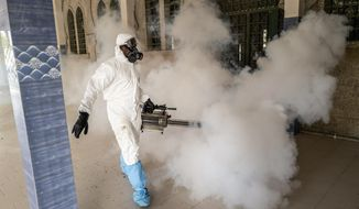 In this Wednesday, April 1, 2020, photo, a municipal worker sprays disinfectant in a mosque to help curb the spread of the new coronavirus in Dakar, Senegal. The new coronavirus causes mild or moderate symptoms for most people, but for some, especially older adults and people with existing health problems, it can cause more severe illness or death. (AP Photo/Sylvain Cherkaoui)