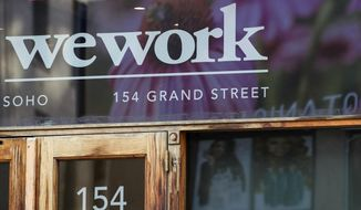 FILE - This Oct. 15, 2019, file photo shows a WeWork logo at the entrance to one of their office spaces in the SoHo neighborhood of New York. Japanese technology company SoftBank Group Corp. ended on Thursday, April 2, 2020,  its tender offer of up to $3 billion worth of shares in office-space rental venture WeWork. (AP Photo/Mary Altaffer, File)