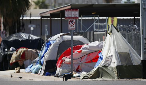 Tents and crude lean-tos crowd the sidewalks where many homeless people live along the streets in record numbers, as concerns grow over the homeless population due to the coronavirus Tuesday, March 24, 2020, in Phoenix. (AP Photo/Ross D. Franklin) ** FILE **