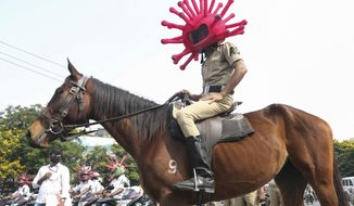An Indian policeman wearing a virus themed helmet rides on a horse during an awareness rally aimed at preventing the spread of new coronavirus in Hyderabad, India, Thursday, April 2, 2020. The new coronavirus causes mild or moderate symptoms for most people, but for some, especially older adults and people with existing health problems, it can cause more severe illness or death. (AP Photo/Mahesh Kumar A.)