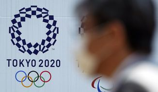 A man wearing a protective face mask walks near the Tokyo 2020 Olympics Thursday, April 2, 2020, in Tokyo. The new coronavirus causes mild or moderate symptoms for most people, but for some, especially older adults and people with existing health problems, it can cause more severe illness or death. (AP Photo/Eugene Hoshiko)