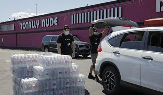 Michael Marowski, right, and Josh Drescher hand out free cases of water at the Little Darlings strip club Wednesday, April 1, 2020, in Las Vegas. The strip club, which has been closed amid the coronavirus pandemic, gave away water for a second day free to anyone who drove through. (AP Photo/John Locher)