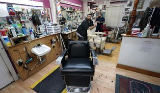 FILE - In this Friday, March 20, 2020 file photo, Carlos Vasquez, left, and his nephew, R.J. Vasquez, wait for customers at their family's barber shop in Houston. They estimate they have lost nearly half of their business due to the COVID-19 coronavirus. (AP Photo/David J. Phillip)