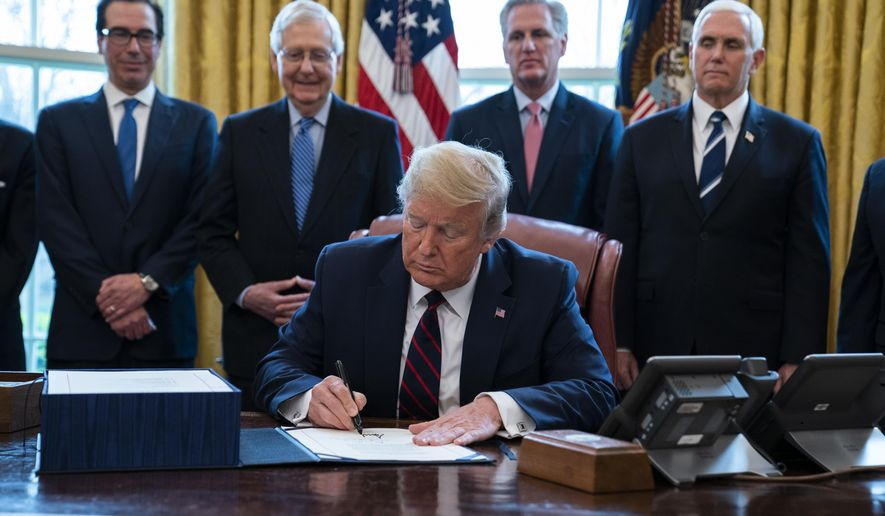 President Donald Trump signs the coronavirus stimulus relief package in the Oval Office at the White House, Friday, March 27, 2020, in Washington, as Treasury Secretary Steven Mnuchin, Senate Majority Leader Mitch McConnell, R-Ky., House Minority Leader Kevin McCarty, R-Calif., and Vice President Mike Pence watch. (AP Photo/Evan Vucci)