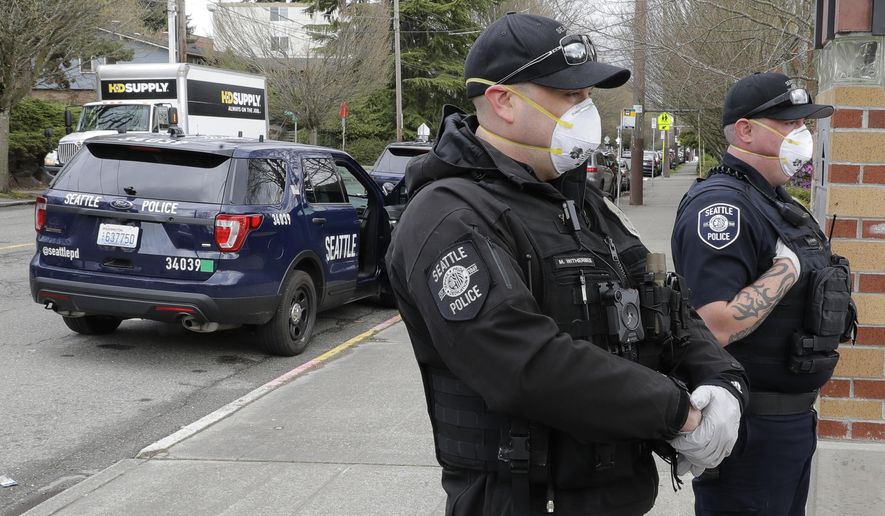 Seattle Police officers wear N95 masks as they listen to conversation during a routine call Thursday, April 2, 2020, in Seattle. As police and fire departments across the country face personnel shortages due to the spread of the new coronavirus, masks and other protective gear are being used to keep officers and firefighters still on the streets safe and healthy. (AP Photo/Ted S. Warren)