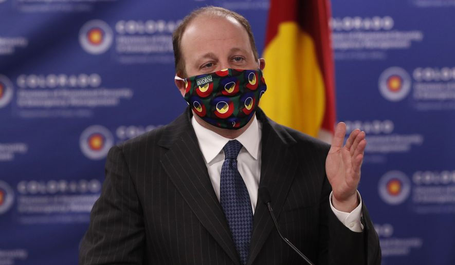 Colorado Gov. Jared Polis dons a mask to encourage state residents to wear them while in public as a statewide stay-at-home order remains in effect in an effort to reduce the spread of the new coronavirus Friday, April 3, 2020, in Centennial, Colo. (AP Photo/David Zalubowski)