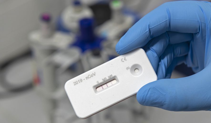A scientist presents an antibody test for coronavirus in a laboratory of the Leibniz Institute of Photonic Technology (Leibniz IPHT) at the InfectoGnostics research campus in Jena, Germany, Friday, April 3, 2020. An international team of researchers with the participation of the Jena Leibniz Institute of Photonic Technology (Leibniz IPHT) has developed a rapid antibody test for the new coronavirus. By means of a blood sample, the test shows within 10 minutes whether a person is acutely infected with the SARS-CoV-2 virus (IgM antibody) or already immune to it (IgG antibody). (AP Photo/Jens Meyer)