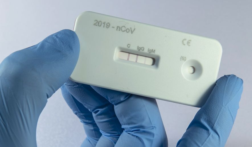 A scientist presents an antibody test for coronavirus in a laboratory of the Leibniz Institute of Photonic Technology (Leibniz IPHT) at the InfectoGnostics research campus in Jena, Germany, Friday, April 3, 2020. An international team of researchers with the participation of the Jena Leibniz Institute of Photonic Technology (Leibniz IPHT) has developed a rapid antibody test for the new coronavirus. (AP Photo/Jens Meyer)