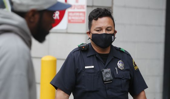 Practicing social distancing amid COVID-19 concerns, Dallas  Police officer R. Salgado looks on while a man speaks in downtown Dallas, Friday, April 3, 2020. New federal guidelines are also expected soon on wearing face masks to help curb the spread of the virus, Trump said recently, adding that the guidance won't require all Americans to use face coverings. For most people, the coronavirus causes mild or moderate symptoms, such as fever and cough that clear up in two to three weeks. For some, especially older adults and people with existing health problems, it can cause more severe illness, including pneumonia and death. (AP Photo/LM Otero)