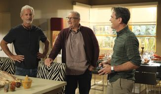 """This image released by ABC shows, from left, executive producer Christopher Lloyd, and actors Ed O'Neill and Ty Burrell on the set of """"Modern Family."""" ABC's """"Modern Family"""" ends its 11-season run with a two-hour finale on Wednesday. (Tony Rivetti/ABC via AP)"""