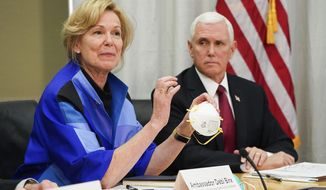 """FILE - In this March 5, 2020, file photo, Dr. Deborah Birx, Ambassador and White House coronavirus response coordinator, holds a 3M N95 mask as she and Vice President Mike Pence visit 3M headquarters in Maplewood, Minn., in a meeting with the company's leaders and Minnesota Gov. Tim Walz to coordinate response to the COVID-19 coronavirus. On Friday, April 3, 2020, the manufacturing giant pushed back against criticism from Trump over production of face masks that are badly needed by American health care workers. 3M said the administration asked it to stop exporting medical-grade masks to Canada and Latin America, which the company said raises """"significant humanitarian implications"""" and will backfire by causing other countries to retaliate against the U.S. (Glen Stubbe/Star Tribune via AP, File)/Star Tribune via AP)"""