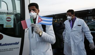 Medics and paramedics from Cuba arrive at the Malpensa airport of Milan, Italy, Sunday, March 22, 2020. 53 doctors and paramedics from Cuba arrived in Milan to help with coronavirus treatment in Crema. For most people, the new coronavirus causes only mild or moderate symptoms. For some it can cause more severe illness, especially in older adults and people with existing health problems. (AP Photo/Antonio Calanni)