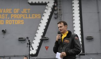 In this Nov. 15, 2019, photo U.S. Navy Capt. Brett Crozier, then commanding officer of the aircraft carrier USS Theodore Roosevelt (CVN 71), addresses the crew during an all-hands call on the ship's flight deck while conducting routine operations in the Eastern Pacific Ocean. U.S. defense leaders are backing the Navy's decision to fire the ship captain who sought help for his coronavirus-stricken aircraft carrier, even as videos showed his sailors cheering him as he walked off the vessel. Videos went viral on social media Friday, April 3, 2020, showing hundreds of sailors gathered on the ship chanting and applauding Navy Capt. Brett Crozier as he walked down the ramp, turned, saluted, waved and got into a waiting car. (U.S. Navy Photo by Mass Communication Specialist 3rd Class Nicholas Huynh via AP) **FILE**