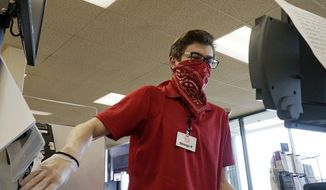 A cashier works at a register as he covers his face with a bandana at a Jewel Osco grocery store in Mount Prospect, Ill., Saturday, April 4, 2020. (AP Photo/Nam Y. Huh)